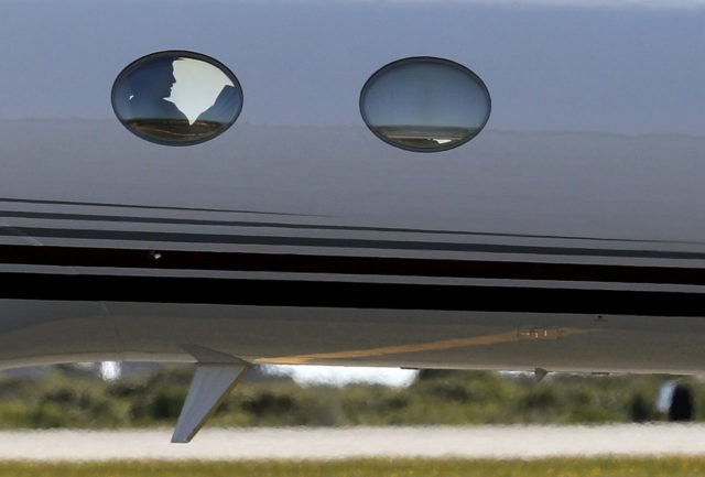 Democratic presidential candidate Hillary Clinton is seen silhouetted in the window of her campaign plane as she arrives at Nantucket Memorial Airport in Nantucket, Mass., Saturday, Aug. 20, 2016., en route to a fundraiser. (AP Photo/Carolyn Kaster)