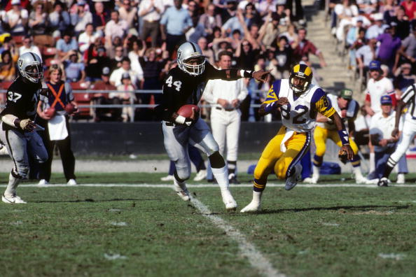 LOS ANGELES - DECEMBER 18: Defensive end Burgess Owens #44 of the Los Angeles Raiders runs with the ball past wide receiver Willie Miller #82 of the Los Angeles Rams during the game at the Los Angeles Memorial Coliseum on December 18, 1982 in Los Angeles, California. The Raiders won …