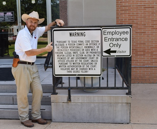Terry Holcomb outside Waller County Courthouse sign. (Photo: Lana Shadwick/Breitbart Texas)