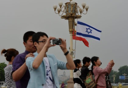 Chinese tourists watch the motorcade of Israeli Prime Minister Benjamin Netanyahu as he arrives to meet the Chinese President Xi Jinping at the Great Hall of the People in Beijing on May 9, 2013. Netanyahu is on a five day visit to China and will meet with Chinese President Xi …