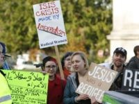 Supporters of refugees counter-protest an anti-refugee group gathered on the steps of the state capitol to protest Gov. Jay Inslee's welcoming of all refugees in Olympia, Washington on November 20, 2015. One week after terror struck in Paris, the attacks dominate the US political debate as President Barack Obama struggles to calm 'hysteria' targeting Syria refugees and Muslims, and his adversaries slam his anti-jihadist strategy as too little, too late. The Republican and Democratic parties, each pressing their own agenda, have seized on the deadly attacks to call for reforms on US policies ranging from refugees, immigration and military strategy in the Middle East to intelligence sharing, firearms and more. AFP PHOTO/ JASON REDMOND (Photo credit should read )