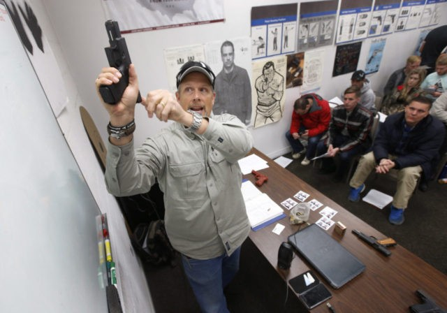 SPRINGVILLE, UT - JANUARY 9: Gun instructor Mike Stilwell, demonstrates an semi automatic hand gun as as he teaches a packed class to obtain the Utah concealed gun carry permit, at Range Master of Utah, on January 9, 2016 in Springville, Utah. Utahs permits, available for a fee to non-residents …