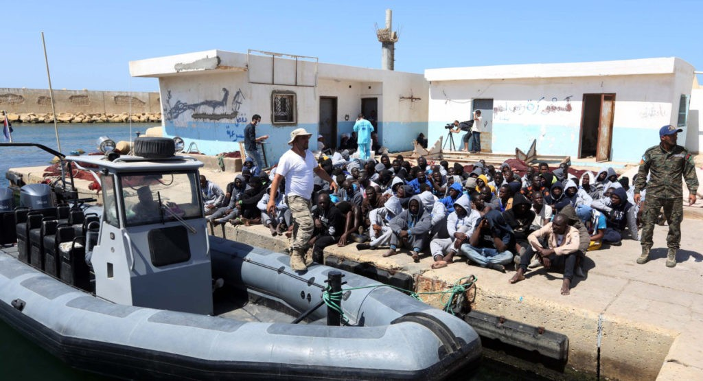 Illegal migrants sit on the dock at the Tripoli port after 117 migrants of African origins, including six pregnant women, were rescued by two coast guard boats off the coast of Libya on June 7, 2016. People smugglers have exploited the chaos gripping Libya since the 2011 uprising that overthrew dictator Moamer Kadhafi to traffic migrants across the Mediterranean Sea to Europe. It is a lucrative business for the smugglers who cram migrants into boats that are small and unsafe for the perilous journey to Italy just 300 kilometres (190 miles) from Libya's shores. / AFP / MAHMUD TURKIA        (Photo credit should read MAHMUD TURKIA/AFP/Getty Images)