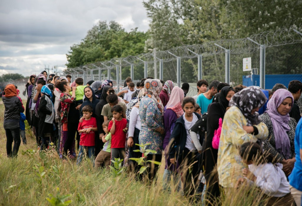 HORGOS, SERBIA - JULY 16: Migrants queue for food being delivered by volunteers at a camp besides the border fence close to the E75 Horgas border crossing between Serbia and Hungary on July 16, 2016 in Horgos, Serbia. Serbia has announced that it will start joint army and police patrols on its borders with Bulgaria and Macedonia to curb the illegal entry of migrants and people smuggling. The decision comes days after EU member Hungary began sending back to Serbia all illegal migrants caught within five miles of the border fence that was constructed last year. The new rules have led to hundreds of migrants being stranded along the Serbia-Hungary border. (Photo by Matt Cardy/Getty Images)