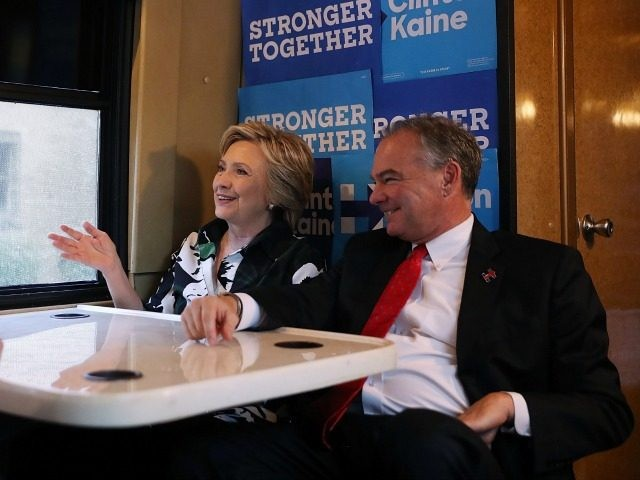 : Democratic presidential nominee former Secretary of State Hillary Clinton (L) and democratic vice presidential nominee U.S. Sen Tim Kaine (D-VA) (R) sit on their campaign bus after attending church services Amani Temple Ministries on July 31, 2016 in Cleveland, Ohio. Hillary Clinton and Tim Kaine are wrapping up their …