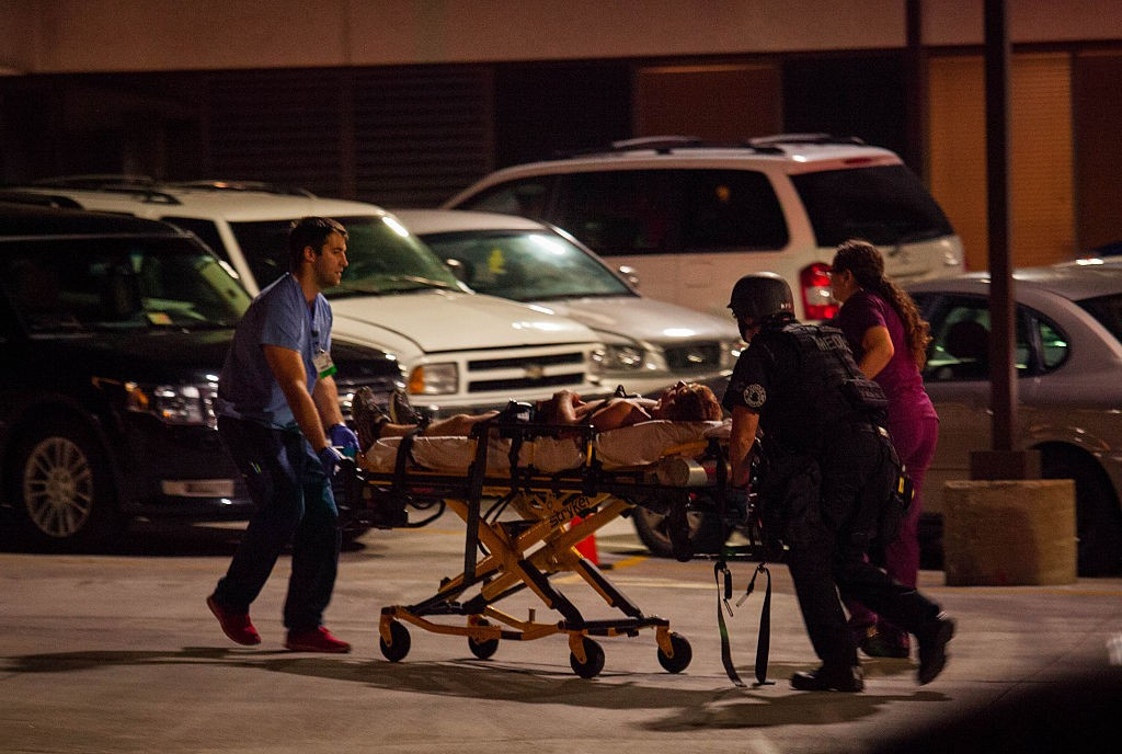 MILWAUKEE, WI - AUGUST 14: Police take a man to a hospital after he was shot in the neck as angry crowds took to the streets for a second night to protest an officer-involved killing August 14, 2016 in Milwaukee, Wisconsin. Protestors threw rocks and there was gunfire in the crowd as hundreds of people confronted police after an officer shot and killed a fleeing armed man earlier in the day. (Photo by Darren Hauck/Getty Images)