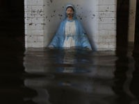ST AMANT, LA - AUGUST 18: A Virgin Mary statue is seen in front of a flooded home on August 18, 2016 in St Amant, Louisiana. Last week Louisiana was overwhelmed with flood water causing at least thirteen deaths and thousands of homes damaged by the flood waters. (Photo by …