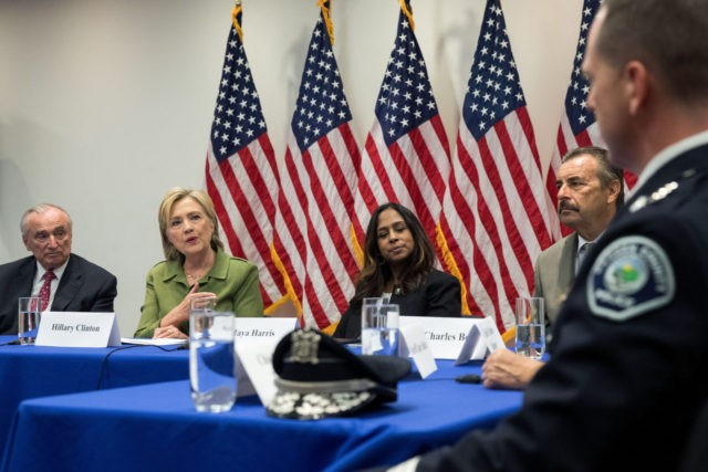 NEW YORK, NY - AUGUST 18: Flanked by Bill Bratton (L), commissioner of the New York City Police Department, and policy advisor Maya Harris (R) look on as Democratic presidential candidate Hillary Clinton delivers opening remarks during a meeting with law enforcement officials at the John Jay College of Criminal …