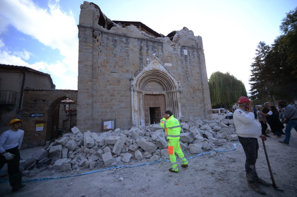 People stand in front of a damaged church in Amatrice on August 24, 2016 after a powerful earthquake rocked central Italy. The earthquake left 38 people dead and the total is likely to rise, the country's civil protection unit said in the first official death toll. Scores of buildings were reduced to dusty piles of masonry in communities close to the epicentre of the quake, which had a magnitude of between 6.0 and 6.2, according to monitors. / AFP / FILIPPO MONTEFORTE (Photo credit should read FILIPPO MONTEFORTE/AFP/Getty Images)