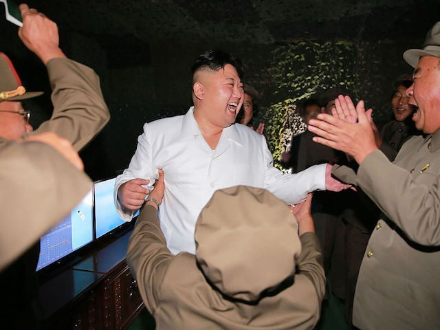 This undated picture released from North Korea's official Korean Central News Agency (KCNA) on August 25, 2016 shows North Korean leader Kim Jong-Un (C) laughing as he inspects a test-fire of strategic submarine-launched ballistic missile at an undisclosed location. / AFP / KCNA / KNS / South Korea OUT / …