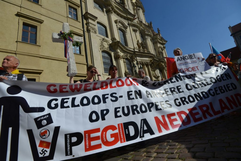 Members and supporters of Pegida (Patriotic Europeans Against the Islamisation of the West) from Netherlans hold a banner during a demonstration against German Chancellor Angela Merkel during her visit in Czech Republic on August 25, 2016 in Prague. / AFP / Michal Cizek (Photo credit should read MICHAL CIZEK/AFP/Getty Images)