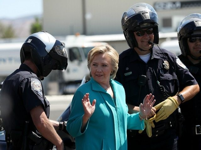 Democratic presidential nominee former Secretary of State Hillary Clinton talks with Reno police officers before getting onto her plane at Reno Tahoe International Airport on August 25, 2016 in Reno, Nevada.