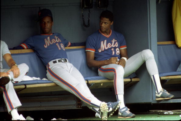 PITTSBURGH - AUGUST 1984: Pitcher Dwight Gooden #16 and outfielder Darryl Strawberry #18 of the New York Mets look on from the dugout during a game against the Pittsburgh Pirates at Three Rivers Stadium in August 1984 in Pittsburgh, Pennsylvania. (Photo by George Gojkovich/Getty Images)
