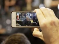 Hillary on iPhone (Charlie Niebergall / Associated Press)