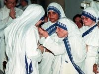 NEW YORK, UNITED STATES: A nun who has just professed her vows to the the Missionaries of Charity kisses the cross as Mother Teresa presents it to her during a ceremony in a church in the Bronx, New York 11 June. Five nuns entered the Missionary and five more renewed …