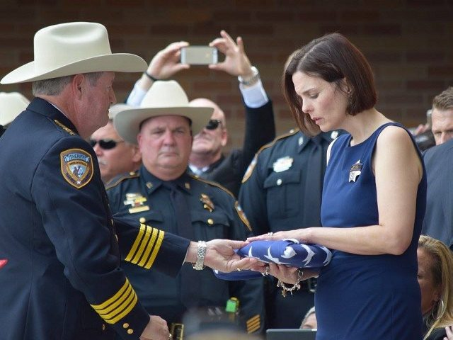 The widow of Deputy Goforth receives the flag that draped her husband's casket from Sheriff Ron Hickman. (Photo: Breitbart Texaas/Bob Price)