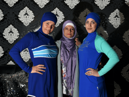 Models clad in burqini swimsuits pose for photos with Australian-Lebanese designer Aheda Zanetti (C) in western Sydney on August 19, 2016. The light-weight, quick-drying two-piece swimsuit which covers the body and hair has been banned from French beaches by several mayors in recent weeks following deadly attacks linked to Islamic …