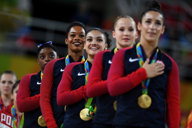 RIO DE JANEIRO, BRAZIL - AUGUST 09: (L to R) Gold Medalists Simone Biles, Gabrielle Douglas, Lauren Hernandez, Madison Kocian and Alexandra Raisman of the United States stand on the podium for the national anthem at the medal ceremony for the Artistic Gymnastics Women's Team Final on Day 4 of …