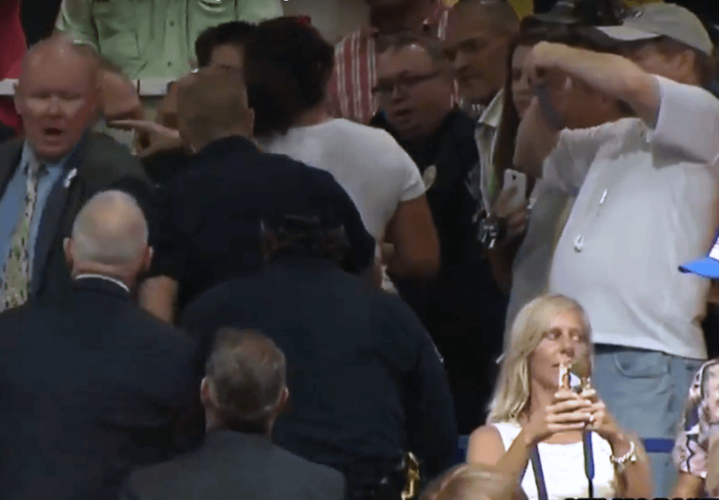 Protester (woman in back wearing white shirt) is escorted out after allegedly disrupting Trump rally. (Photo: Trump Rally Video Screenshot)