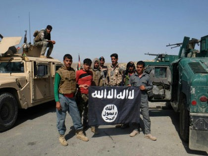 Afghan police poses for photograph with an Islamic State flag after an operation in the Kot district of Jalalabad province east of Kabul, Afghanistan, Monday, Aug. 1, 2016, (AP Photo/Melad Hamedi)