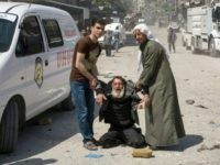 A man in a state of shock receives help on a street following a reported airstrike on April 23, 2016 in the rebel-held neighbourhood of Tareeq al-Bab in the northern city of Aleppo. The barrage of air strikes on Aleppo began around 10:00 local time and hit several neighbourhoods, including the heavily-populated Bustan al-Qasr district, an AFP correspondent in the city said. But the deadliest raid was on the Tareeq al-Bab neighbourhood on the eastern edges of the city. / AFP / KARAM AL-MASRI (Photo credit should read KARAM AL-MASRI/AFP/Getty Images)
