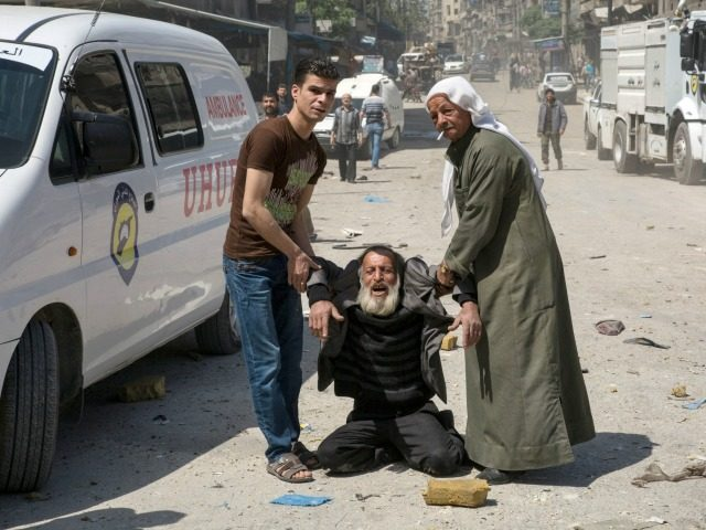 A man in a state of shock receives help on a street following a reported airstrike on April 23, 2016 in the rebel-held neighbourhood of Tareeq al-Bab in the northern city of Aleppo. The barrage of air strikes on Aleppo began around 10:00 local time and hit several neighbourhoods, including …