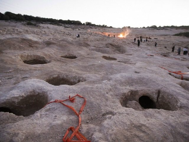 Ultra-Orthodox Jews stand at the site where religious men say Jewish graves are located in ancient tombs as they demonstrate against the removal of the tombs due to construction plans in the city of Beit Shemesh, on February 12, 2014. AFP PHOTO / JACK GUEZ (Photo credit should read JACK …