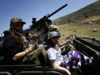 Gun fun: Danny Josephson, left, and his wife Jesse, right, ride in his father Kent Josephson's 1953 Willys Jeep with a Browning .30 calibre machine gun attached during the Big Sandy Shoot in Mohave County, Arizona