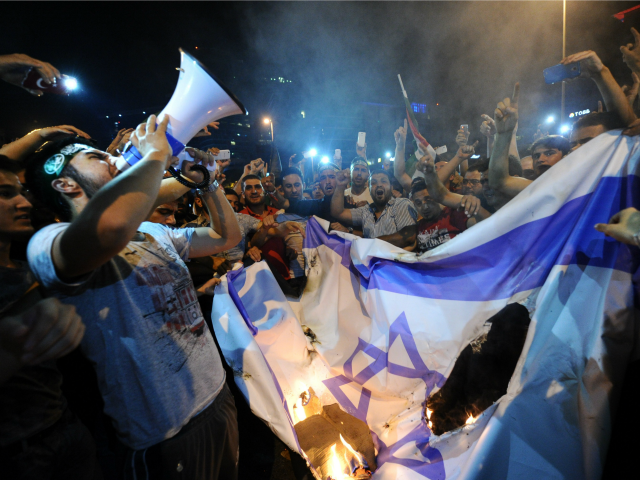 Turkish protestors set fire to Israel flag while they are shout slogans during a demonstration to denounce the Israeli military operations in Gaza on July 19, 2014 in front of the Israeli Consulate in Istanbul. Israel decided to pull some of its diplomatic staff out of Turkey in the wake …