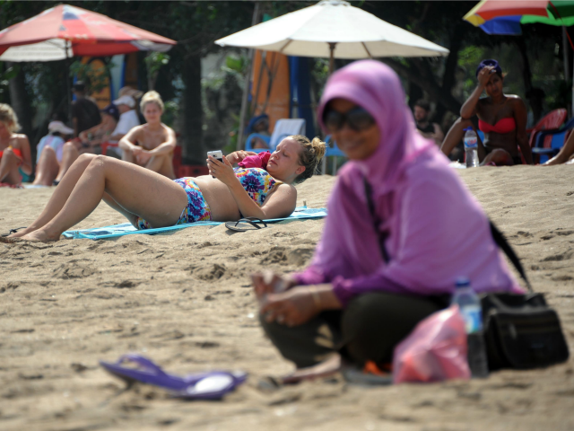 A Muslim woman wearing a veil sits in front of foreign tourists wearing bikinis on Kuta beach in Bali on June 6, 2013. Contestants at this year's Miss World beauty pageant will not wear bikinis in the parade in a bid to avoid causing offence in Muslim-majority Indonesia, organisers said …