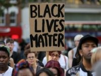 A woman holds up a placard in Altab Ali Park in east London, as she attends a Black Lives Matter event, on August 5, 2016. The group, inspired by the US protest movement against police shootings of black men, has highlighted British deaths in police custody and the fact that black people in Britain are more likely to be arrested and jailed. / AFP / DANIEL LEAL-OLIVAS (Photo credit should read DANIEL LEAL-OLIVAS/AFP/Getty Images)