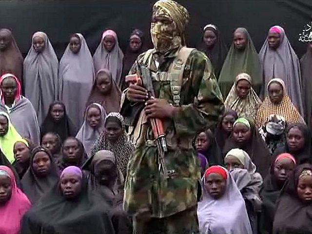 TOPSHOT - This video grab image created on August 14, 2016 taken from a video released on youtube purportedly by Islamist group Boko Haram showing what is claimed to be one of the groups fighters at an undisclosed location standing in front of girls allegedly kidnapped from Chibok in April …