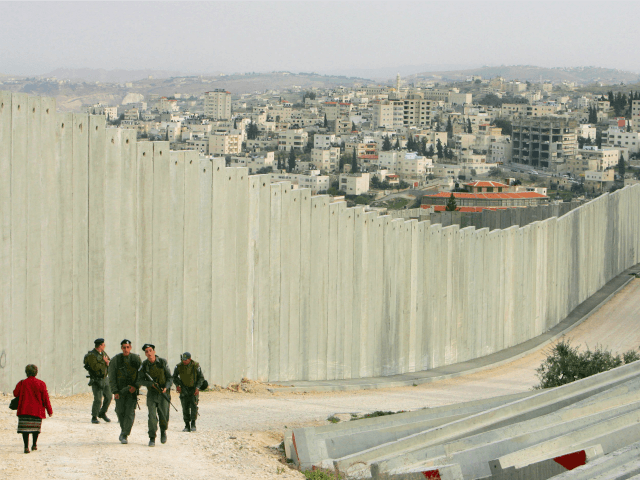 Israeli soldiers patrol along the concrete separation barrier bordering Abu Dis, West Bank March 26, 2006 in East Jerusalem, Israel. The controversial separation barrier blocks direct access between the West Bank and Israel and will eventually separate Jerusalem from the West Bank. The wall, Israel claims, is the most effective …