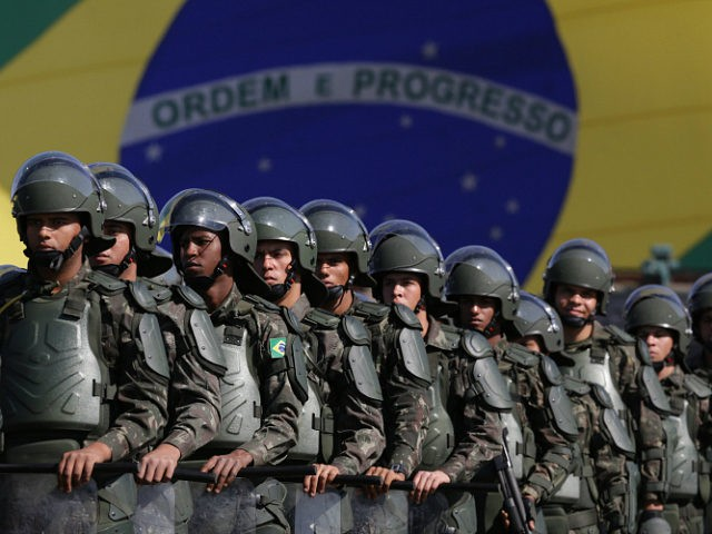FILE - In this July 22, 2016 photo, Brazilian Army soldiers take part in military exercise during presentation of the security forces for the Rio 2016 Olympic Games, in front of the National Stadium, in Brasilia, Brazil. Security has emerged as the top concern during the Olympics, including violence possibly spilling over from Rio's hundreds of slums. Authorities have said 85,000 police officers and soldiers will be patrolling during the competitions. (AP Photo/Eraldo Peres, File)