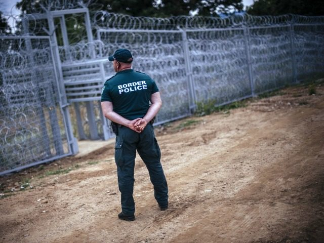 A border policeman stands next to a barbed wire wall on the Bulgarian border with Turkey, near the village of Golyam Dervent on July 17, 2014. Overwhelmed by an influx of mostly Syrian immigrants, Bulgaria has taken steps to secure its EU border -- including building a barbed-wire fence -- …