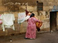 "CAIRO, EGYPT - FEBRUARY 26: An Egyptian woman collects her washing which was hung out to dry on the outer wall of the Mamluk 15th century madrasa of Sultan Qaytbay, where an Arabic sign proclaims ""Allah"" over a low doorway, on February 26, 2009 in Cairo, Egypt. Despite being known …"