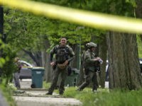 Chicago SWAT officers gather outside a house after rushing the structure where a man suspected of killing a few people had barricaded himself and fired shots at officers on the south side of Chicago on Thursday, May 12, 2016. After hours in a standoff with a man suspected of killing …