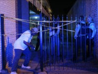 A resident ducks under crime scene tape after retrieving medication from his apartment, as officers guard the area of a police-involved shooting in the apartment complex, on the 1800 block of East 87th Street early Sunday, July 10, 2016, in Chicago. A man in a second floor unit was shot …