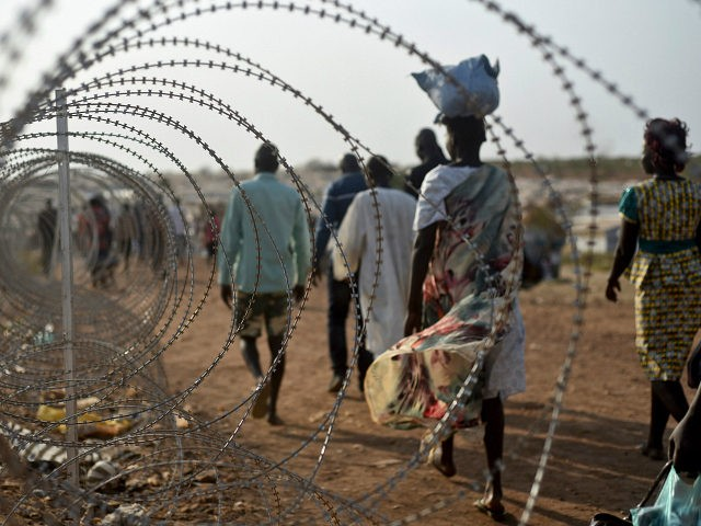FILE - In this Tuesday, Jan. 19, 2016 file photo, displaced people walk next to a razor wire fence at the United Nations base in the capital Juba, South Sudan. According to reports from victims which have come to light Monday Aug. 15, 2016, South Sudanese troops, fresh from winning a battle against opposition forces in the capital, Juba, on July 11, 2016, went on a nearly four-hour rampage through a residential compound popular with foreigners, and the U.N. peacekeeping force stationed nearby are accused of refusing to respond to desperate calls for help. (AP Photo/Jason Patinkin, File)