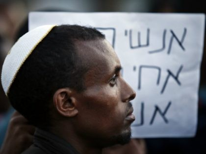 An Ethiopian Israeli protestor wears a kippah, the traditional Jewish skullcap for men, during a demonstration in a street of the Israeli city of Kiryat Gat on May 4, 2015. Israel pledged to crack down on racism and discrimination against Ethiopian Jews as officials sought to ease tensions after a …