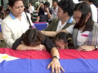 Miriam Templo and her daughters weeps over the flag-draped coffin bearing the remains of Getulio Templo, one of three FIlipino overseas workers killed in a terrorist bombings in Riyadh last month. The bodies arrived at the Ninoy Aquino International AIrport in Manila 02 June 2003, in Manila, the Philippines. AFP PHOTO/Jay DIRECTO (Photo credit should read JAY DIRECTO/AFP/Getty Images)