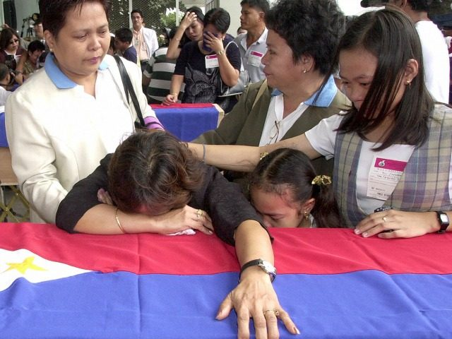 Miriam Templo and her daughters weeps over the flag-draped coffin bearing the remains of Getulio Templo, one of three FIlipino overseas workers killed in a terrorist bombings in Riyadh last month. The bodies arrived at the Ninoy Aquino International AIrport in Manila 02 June 2003, in Manila, the Philippines. AFP …