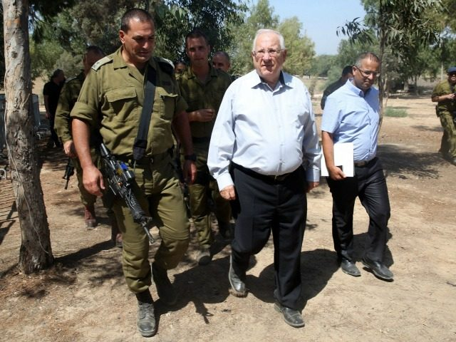 Israeli President Reuven Rivlin (C) is escorted by an army officer as he visits near the Israel-Gaza border area on August 23, 2016. During his visit Rivlin met with Israeli soldiers and was briefed on the security situation along the border. / AFP / MENAHEM KAHANA (Photo credit should read …