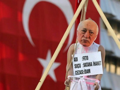 A picture taken on August 2, 2016 shows a picture of US-based preacher Fethullah Gulen set up on a dummy at the Kizilay Square in front of a Turkish national flag in Ankara during a protest against the failed military coup, on August 2, 2016. Erdogan said on August 2, …