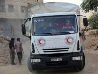 A member of the Syrian Arab Red Crescent (SARC) drives a truck as a convoy of SARC and United Nations' vehicles arrives in the rebel-held area of Harasta on the northeastern outskirts of the capital Damascus on August 29, 2016. / AFP / AMER ALMOHIBANY (Photo credit should read AMER …