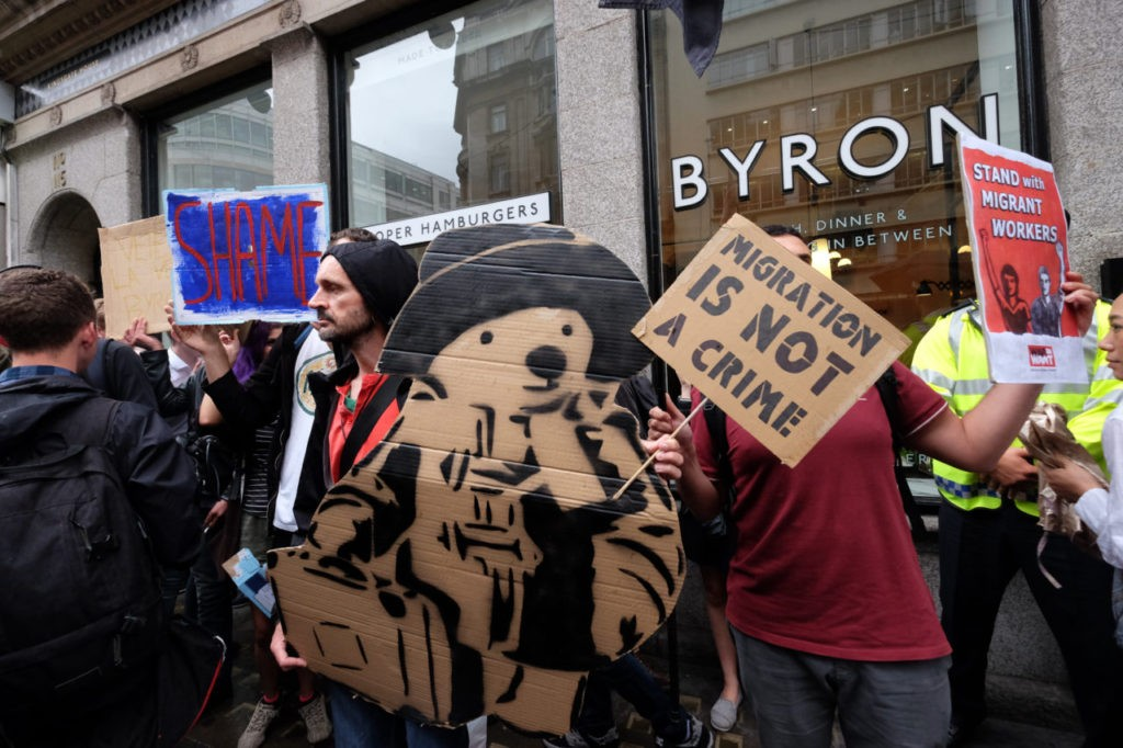 A protester holds a cardboard image of Paddington Bear, a classic children's character who, in the story, hails from Peru.