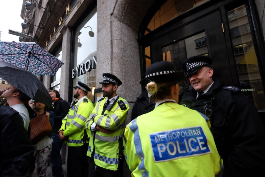 Police stand patiently in the rain