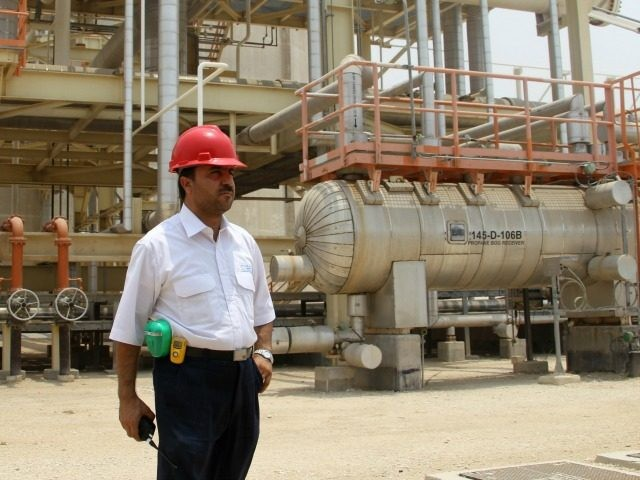 An Iranian worker stands in front of a construction during a visit by Iranian Journalists to the South Pars gas field development phases (5-8) in the southern Iranian port town of Asaluyeh on July 19, 2010 as a top official announced that global energy majors are welcome to help develop …