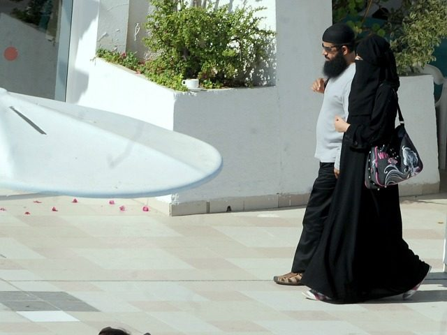 A woman wearing a niqab walks alongside her husband at the pool of a hotel in the Tunisian coastal holiday city of Mahdia, on August 29, 2012. According to some local media, fewer women go to the beach wearing bikinis as they fear attacks by religious extremists after the Islamist …