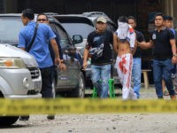 INDONESIA, MEDAN : Indonesian policemen guard a blindfolded suspect who attacked a priest in Medan on August 28, 2016. A knife-wielding attacker in Indonesia stabbed a Catholic priest and tried to set off an explosive device at a church on, police said, the latest in a string of attacks on religious minorities in the mainly Muslim country. / AFP PHOTO / STR